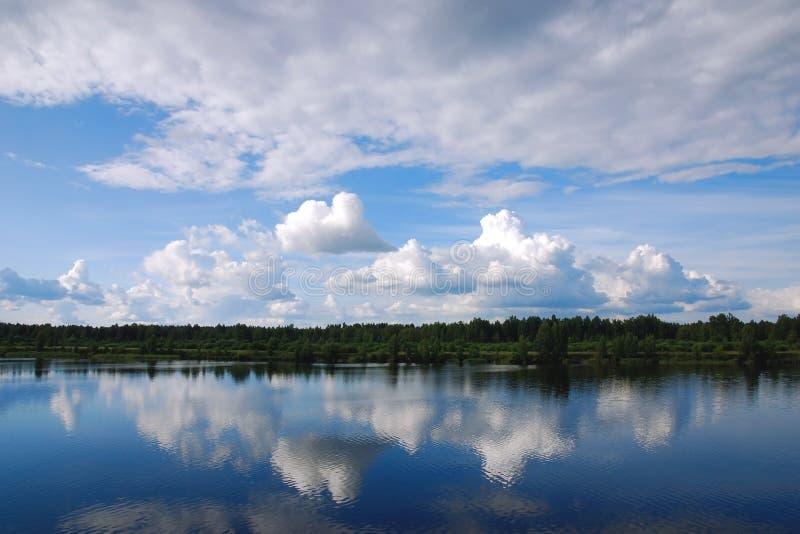 Daglandskap med härliga moln reflekterade i flod- eller sjövattenyttersida Blå sommarhimmel, trevlig varm dag vid vattnet i n royaltyfria bilder