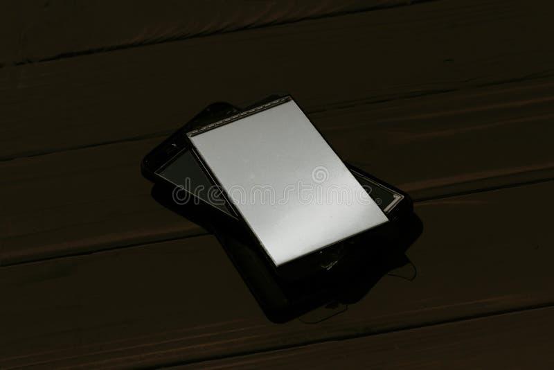 Daglicht Gebroken mobiele telefoon Houten achtergrond heb het stemmen royalty-vrije stock afbeeldingen