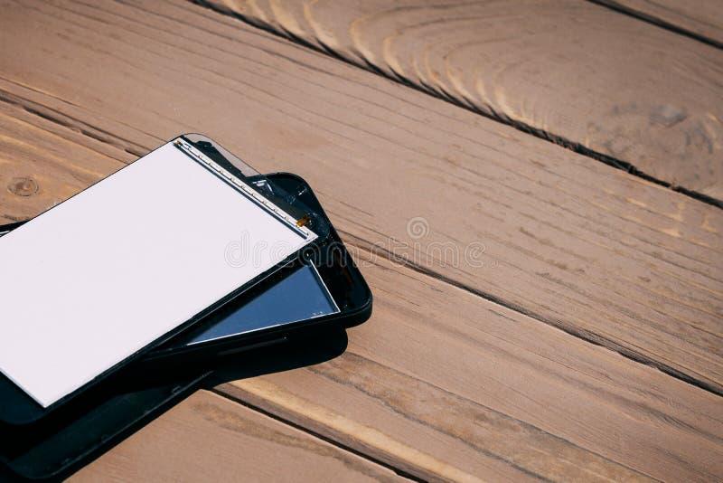 Daglicht Gebroken mobiele telefoon Houten achtergrond heb het stemmen stock fotografie