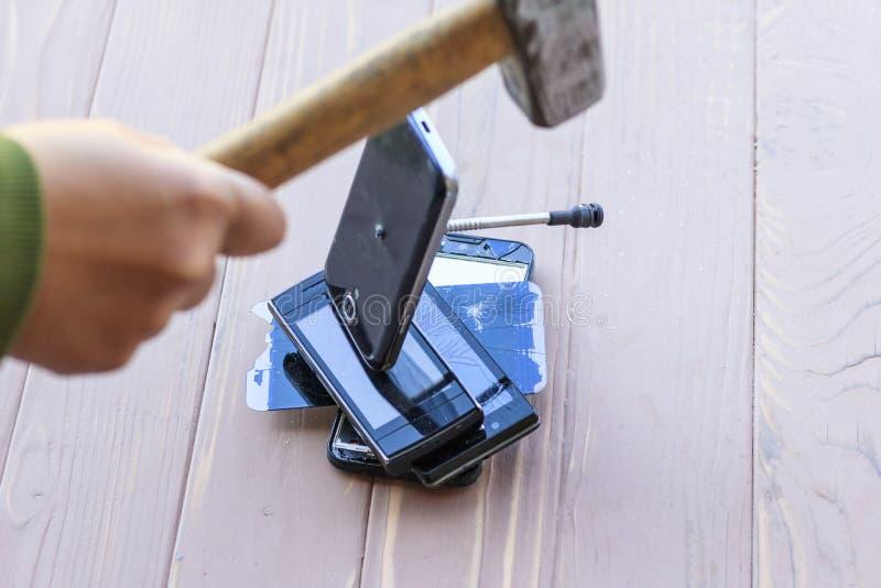 Daglicht hamer die op de telefoons wordt geraakt in één van hen is er een metaalspijker royalty-vrije stock afbeelding