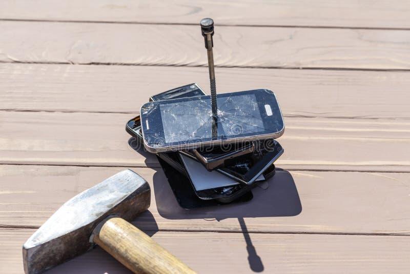Daglicht hamer die op de telefoons wordt geraakt in één van hen is er een metaalspijker stock foto's