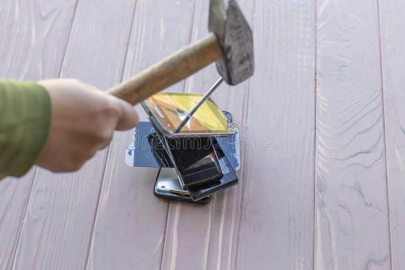 Daglicht hamer op de telefoons wordt geraakt die in één van hen is er een metaalspijker stock afbeelding