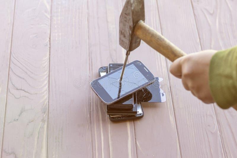 Daglicht hamer op de telefoons wordt geraakt die in één van hen is er een metaalspijker stock fotografie