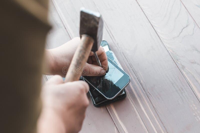 Daglicht hamer op de telefoons wordt geraakt die in één van hen is er een metaalspijker stock foto