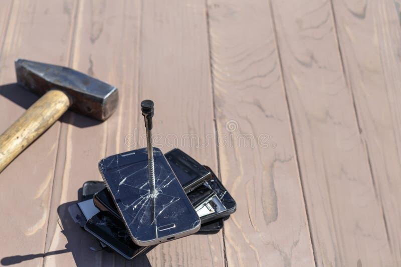 Daglicht hamer op de telefoons wordt geraakt die in één van hen is er een metaalspijker stock foto's