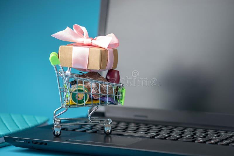 Dagliga köp och gåvor i den shoppa vagnen på bärbar datortangentbordet Begrepp av shopping i online-diversehandel arkivfoton
