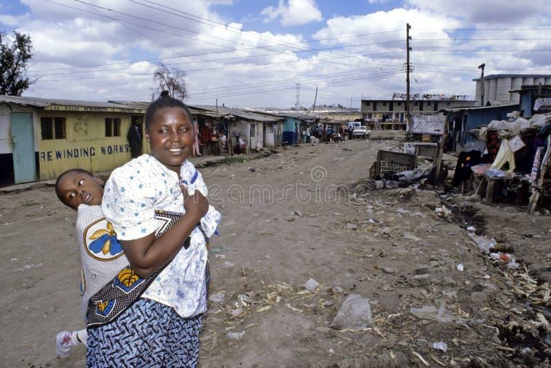 Dagligt livkvinnor med det rörelsehindrade barnet, slumkvarter Nairobi fotografering för bildbyråer