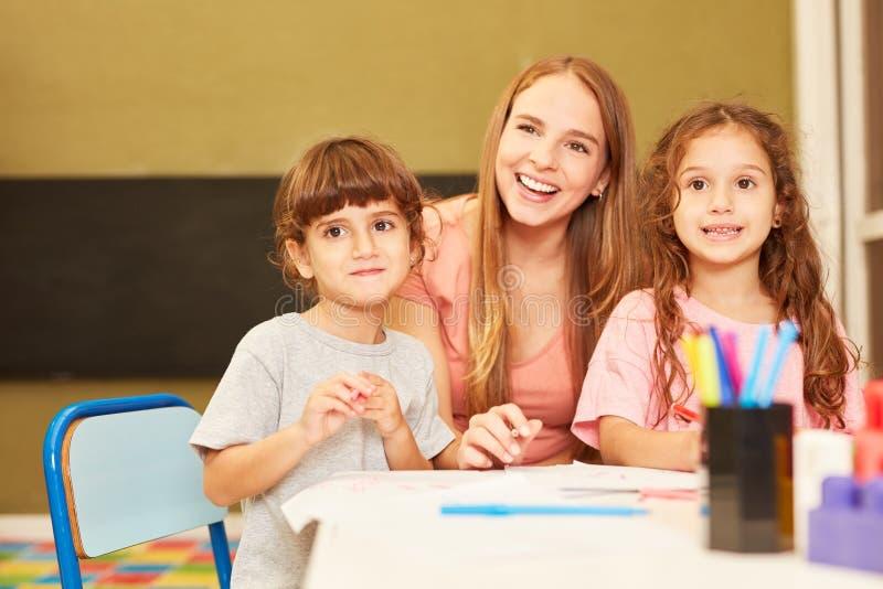 Dagmamma tillsammans med två flickor arkivbild