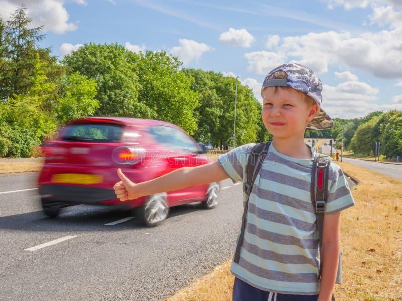Dagmening weinig reiziger van de kindjongen met rugzak die auto op Britse weg halen royalty-vrije stock fotografie