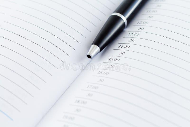 Dagordningplanläggningsdagbok med pennan royaltyfri bild