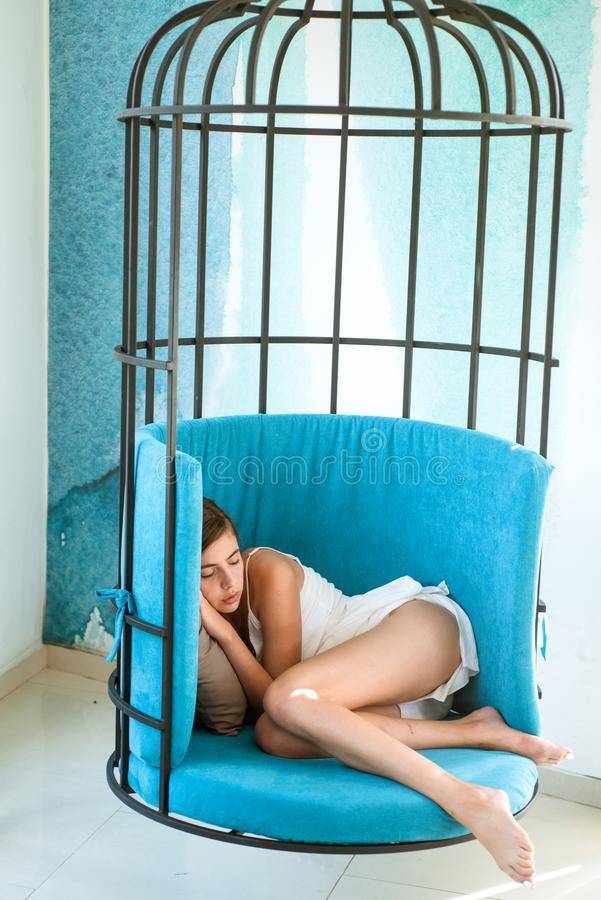 dagslaap van vermoeid meisje als kooivoorzitter Totale ontspanning snoepje en comfortdroom, ochtend vrouwenslaap in ijzerkooi stock foto