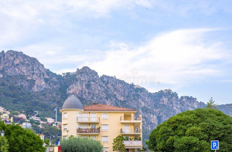Dagsljussikt till ett hotell och stora berg i Beaulieu surmer arkivbild