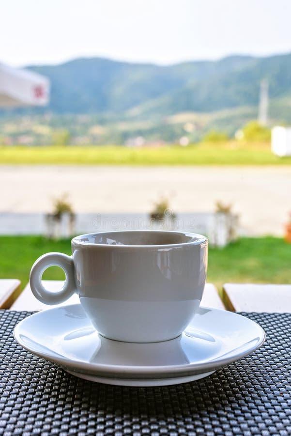 Dagsljussikt till kaffekoppen på tabellen med gröna berg arkivbild