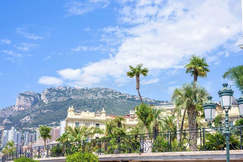 Dagsljussikt till stadsbyggnader, gröna träd och stora berg royaltyfri bild