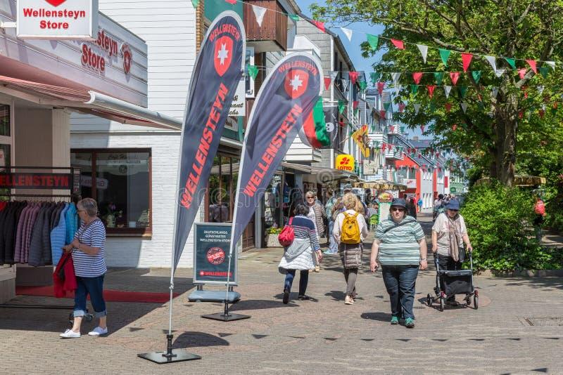 Dagsturister i den huvudsakliga gatan Helgoland som gör skattefri shopping royaltyfria bilder