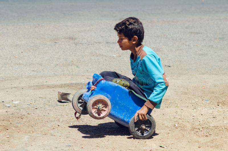 Dahab, Egypt May 11, 2019: little boy rides in a makeshift trolley from a plastic canister stock photography