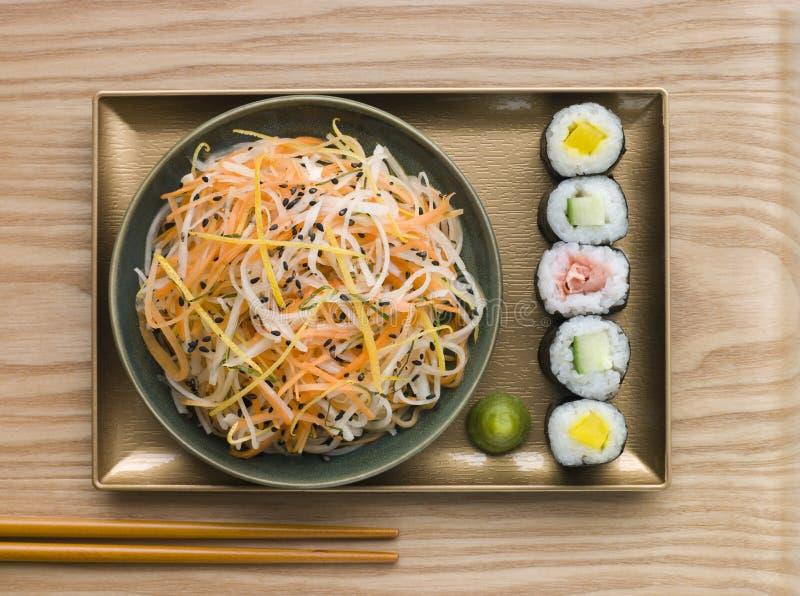 Daikon und Karotte-Salat mit Sesam-Sushi lizenzfreie stockbilder