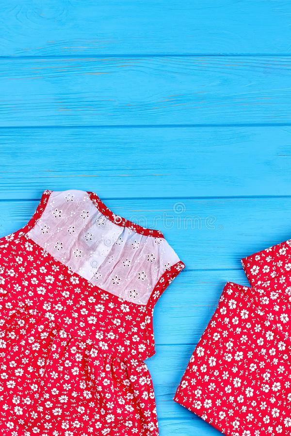 Dainty baby-girl summer clothes. Setting of organic colored clothes for small girls, copy space. Top view of casual kids summer apparel royalty free stock photos