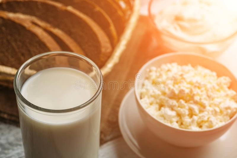 Dairy farm food: curd cheese and cream in bowls, milk and fresh bread, sunlight effect, selective focus stock photo