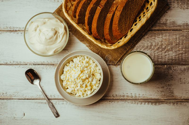 Dairy farm products on wooden table: milk in glass, cottage cheese, sour cream and bread, top view stock images