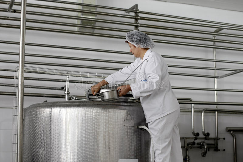 Dairy food production plant. A woman employee is checking the milk from an industrial liquid storage tank in a dairy food production plant royalty free stock photography