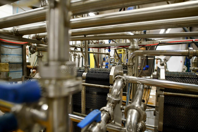 Dairy plant equipment at work close up shot. Automatic modern machinery at dairy production plant in operating position stock photos