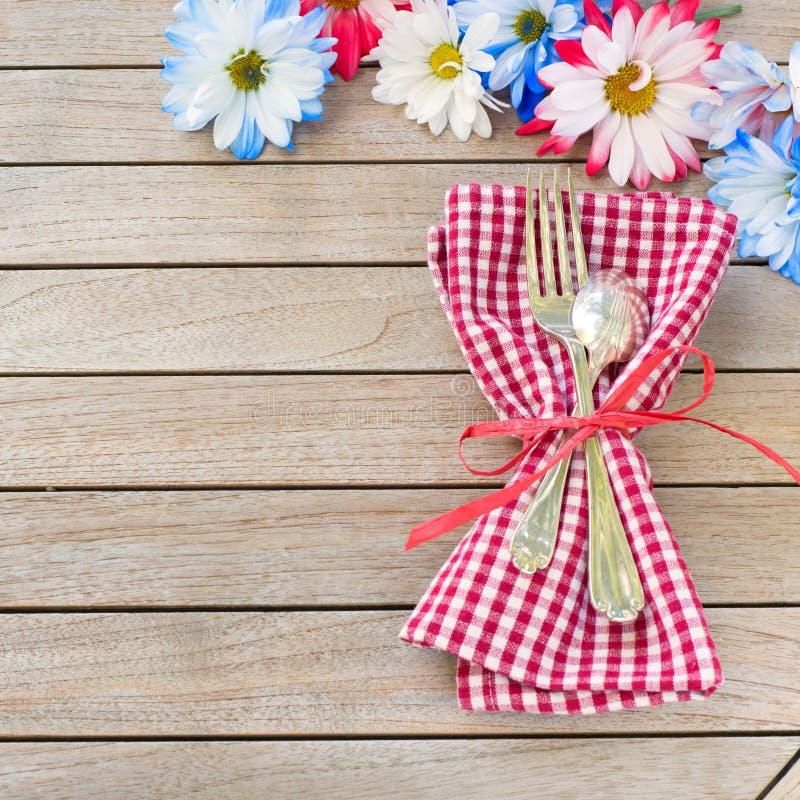 Daisy Flowers in bianco e blu rossi con argenteria ed il tovagliolo che mette su lato della Tabella rustica del bordo con stanza  immagine stock libera da diritti