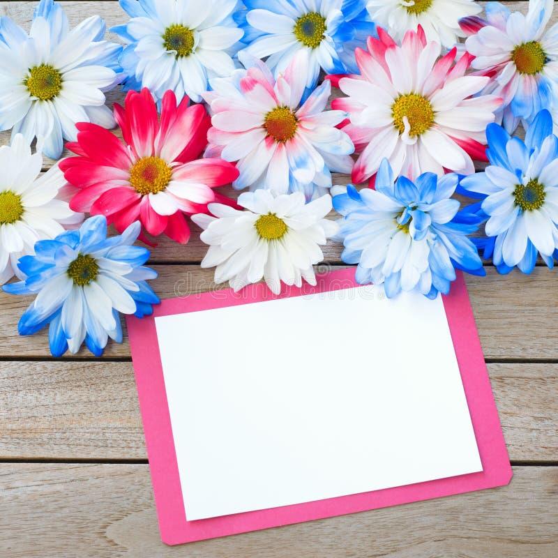 Daisy Flowers in den roten weißen und blauen Farben mit der Partei-Einladungs-Karte, die auf rustikale Brett-Tabelle mit Raum ode lizenzfreie stockfotografie