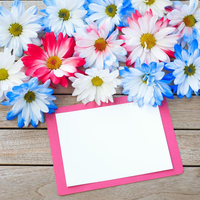Daisy Flowers in Red White and Blue Colors with Party Invitation Card Laying on Rustic Board Table with room or space for your wor royalty free stock photography