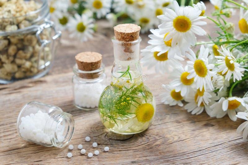 Daisy infusiefles, Kamillebloemen, flessen van homeopathische druppeltjes en kruik van droge madeliefjes stock foto