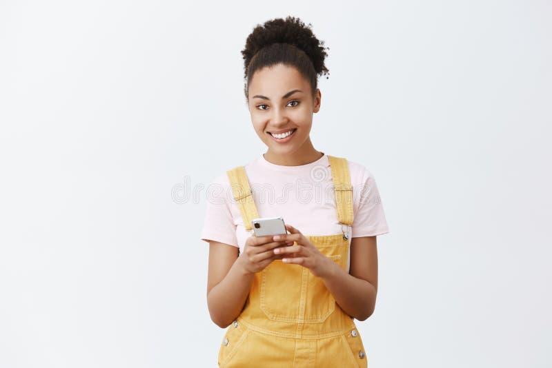daj mi numer twojej Portret czarować flirty i kobiecej ciemnoskórej młodej kobiety w żółtych kombinezonach, trzyma zdjęcie stock