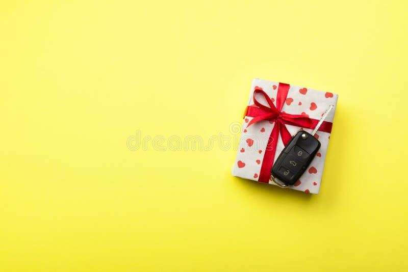Daje prezentowi samochodowemu kluczowemu pojęciu odgórny widok Teraźniejszy pudełko z czerwonym tasiemkowym łęku, serca i samocho obrazy royalty free