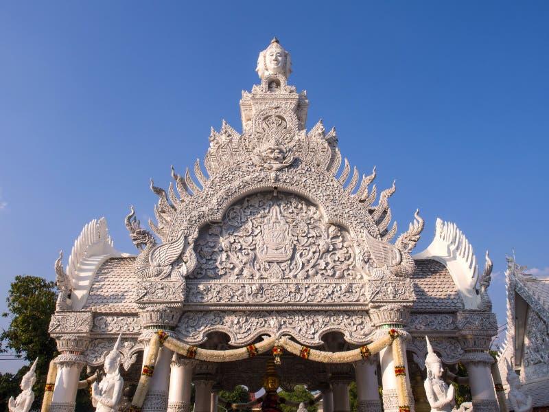 Dak en deurboog Thaise kunst onder blauwe hemel stock afbeelding