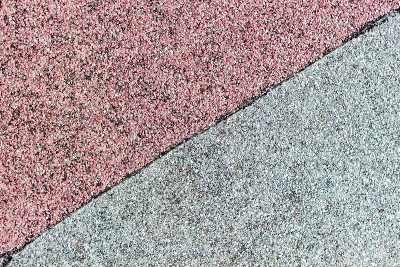 Dak het behandelen van rood en grijs dakwerkmateriaal wordt verdeeld door een zwarte streep langs de diagonaal Ruberoidachtergron stock foto