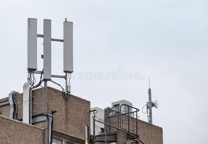 Dak hoogste cellulaire die mededelingen en microgolfantennes boven op een bureaugebouw worden gezien royalty-vrije stock foto