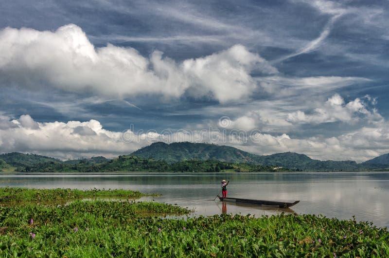 DAK-LAK VIET NAM: De groep Aziatische landbouwer gaat door rijboot aan LAK-meer in de herfsttijd werken, familie van etnische min stock afbeelding