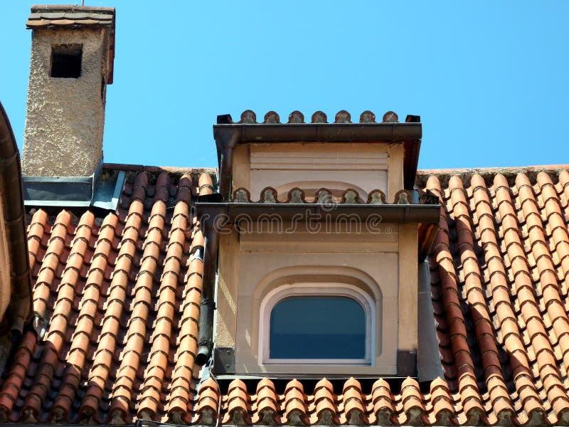 Dak van een middeleeuws huis met de tegels van het koekoekdak en open haard met baksteendekking stock afbeelding