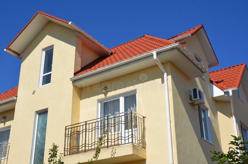 Dak van het huis het rode metaal met zoldervenster, balkon, guttering het probleemgebied van het pijpleidingssysteem Het installe royalty-vrije stock fotografie