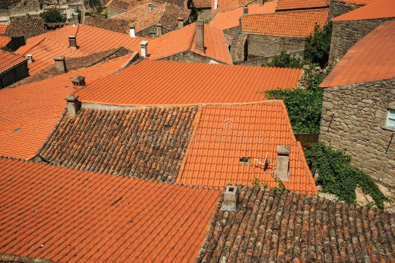 Daken van oude steenhuizen en schoorstenen in Monsanto stock afbeeldingen