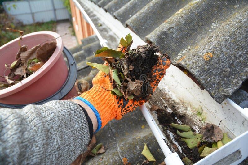 Dakgoot het Schoonmaken van Bladeren in de Herfst met hand De Schoonmakende Uiteinden van de dakgoot royalty-vrije stock foto's