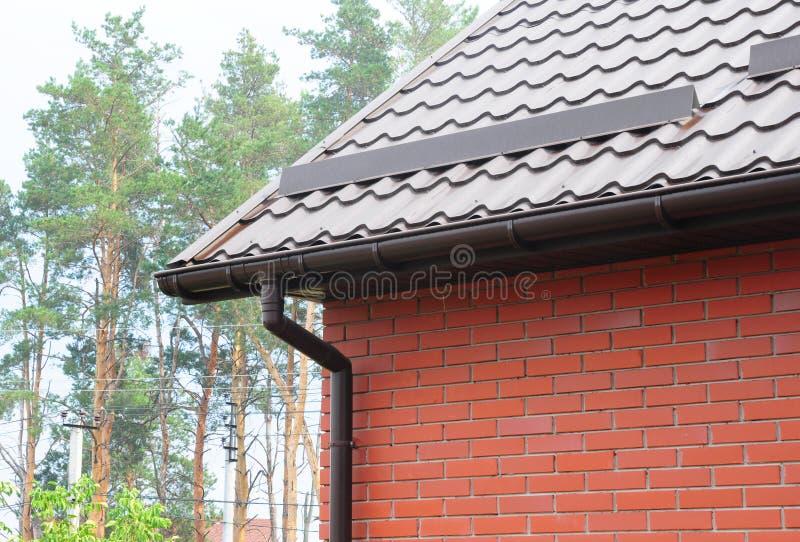 Dakgoot met de raad van de metaalsneeuw voor sneeuwbescherming De bouw van het metaaldakwerk met het guttering royalty-vrije stock afbeeldingen