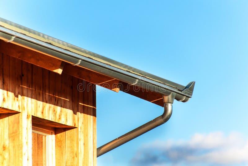 Dakgoot op het dak ecologische huis Zinkgoot op de houtbewerking stock foto's