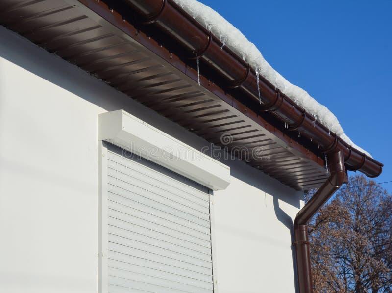 Dakgoothoogtepunt van ijs in de winter De bevroren goot van het ijs binnenshuis dak met witte rolling shutters voor huisbeschermi royalty-vrije stock foto's