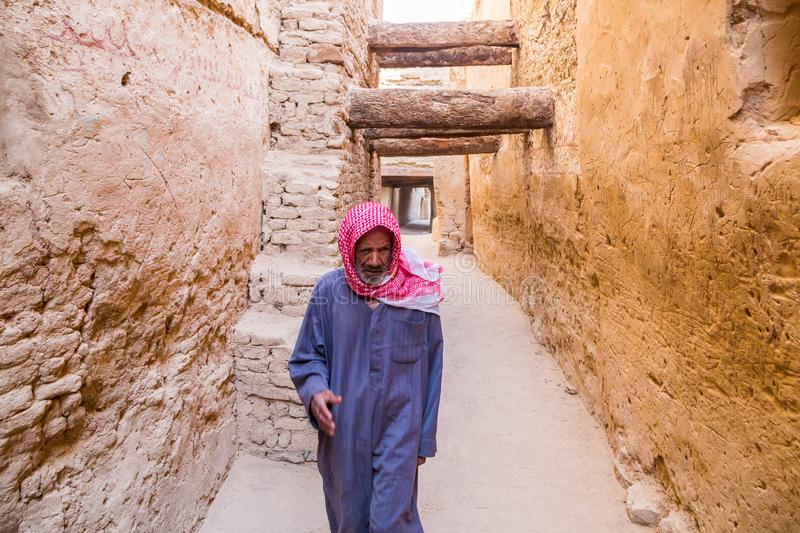 Arab man walking dressed in blue national male dress thawb, medieval street through ancient town in Al Qasr, Dakhla Oasis, Egypt. royalty free stock images