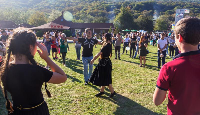 Young guy and girl dancing in the meadow at the Adygei cheese festival in the foothills of the Caucasus. Dakhovskaya, Russia - September 22, 2018: young guy and stock image