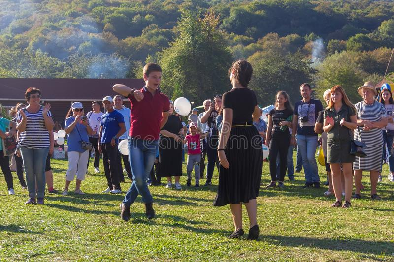 Young guy and girl dancing in the meadow at the Adygei cheese festival in the foothills of the Caucasus. Dakhovskaya, Russia - September 22, 2018: young guy and royalty free stock photos