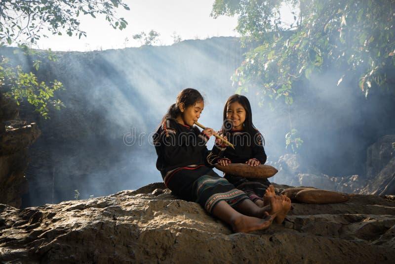 Daklak, Vietnam - 9 de marzo de 2017: Dos niñas de la minoría étnica de Ede que aprendían tocar la flauta en bosque la Ede han vi foto de archivo