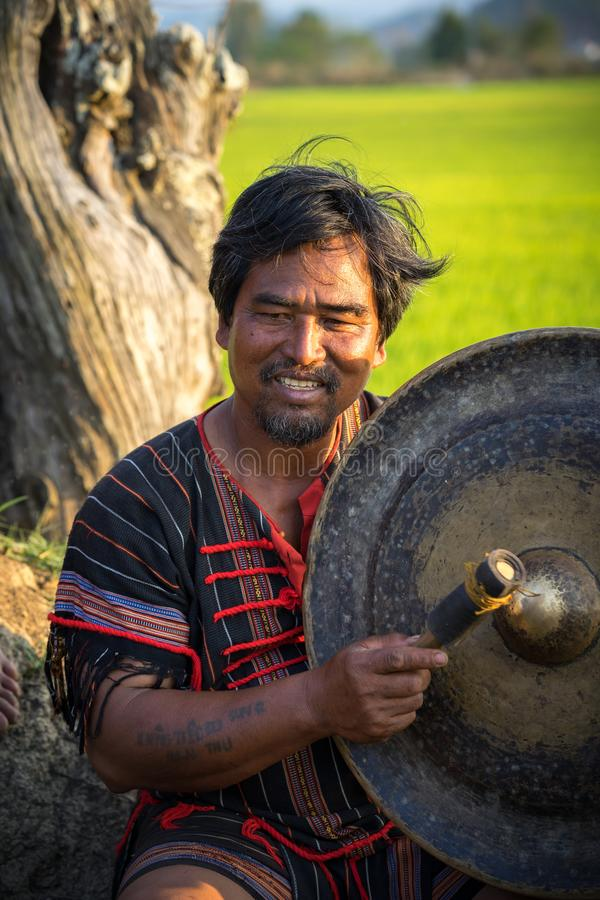 Daklak, Vietnam - Mar 9, 2017: Portrait of minority man in traditional dress knocking a copper gong in forest in Buon Me Thuot royalty free stock photography