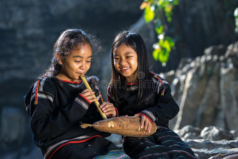 Daklak, Vietnam - Mar 9, 2017: Two Ede ethnic minority little girls learning to play the flute in forest. The Ede have long lived royalty free stock photography