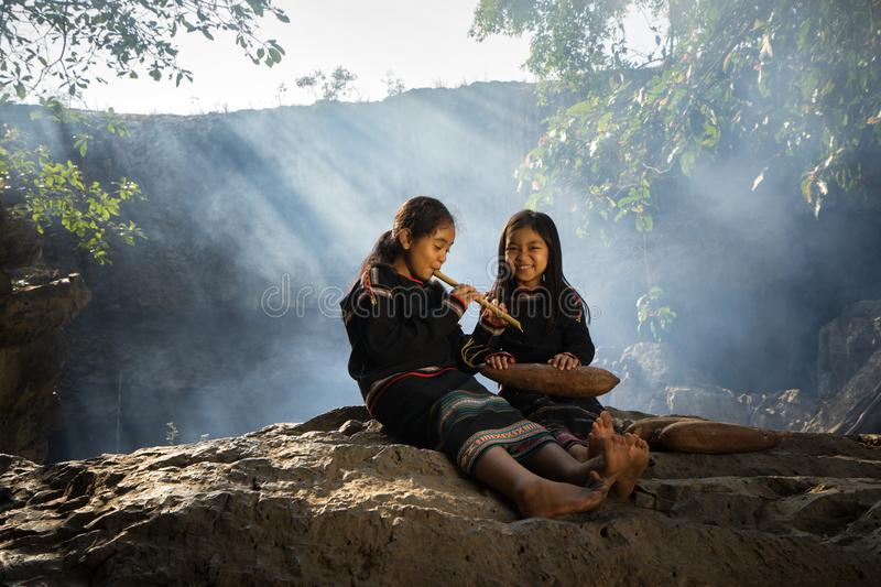 Daklak, Vietnam - Mar 9, 2017: Two Ede ethnic minority little girls learning to play the flute in forest. The Ede have long lived. In the Tay Nguyen or high stock photo